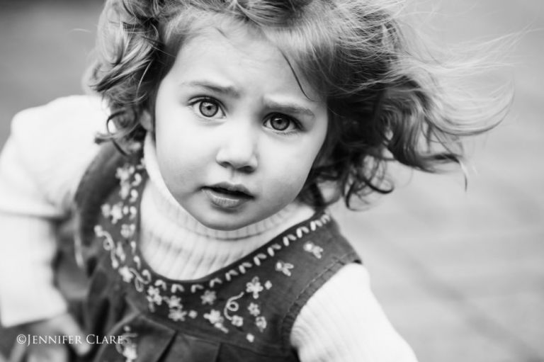 a black and white image of a small girl with a quizzical expression.